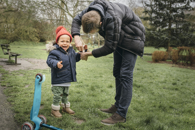Young child cries after fall in muddy grass while father cleans his dirty hand