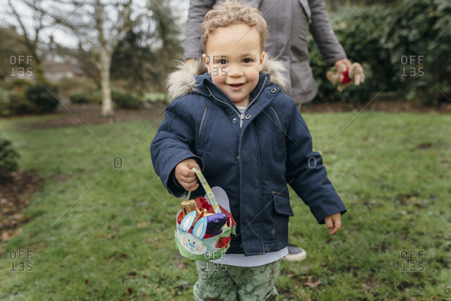 Young boy holding a basket full of Easter chocolate egg
