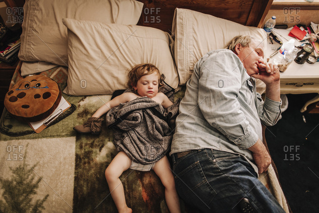 A little girl and grandfather napping on a bed