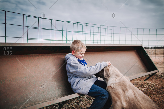A boy petting a dog