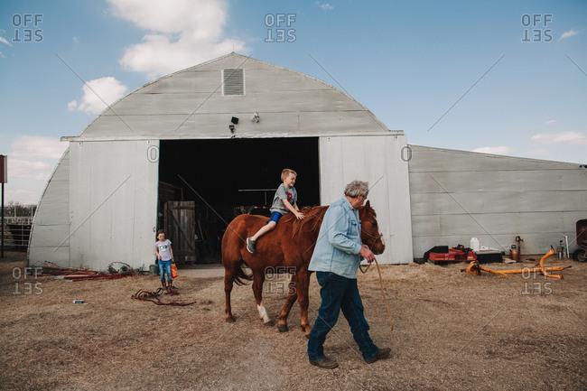 A boy riding a horse led by a man