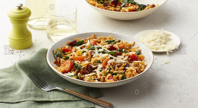 Glass of wine next to chorizo orzo with roasted cherry tomatoes