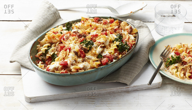 Pan of lasagna baked fusilli on whitewashed cutting board
