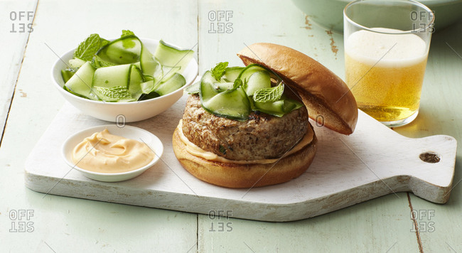 Fusion Thai pork burger topped with mint and shaved zucchini on rustic wooden platter