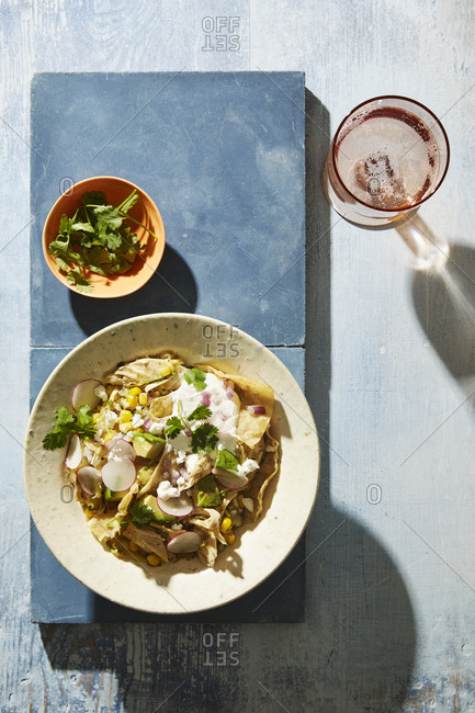 Top view of chilaquiles on thick boards and glass of refreshing rose wine