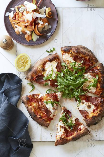 Precut slices of prosciutto pizza from above
