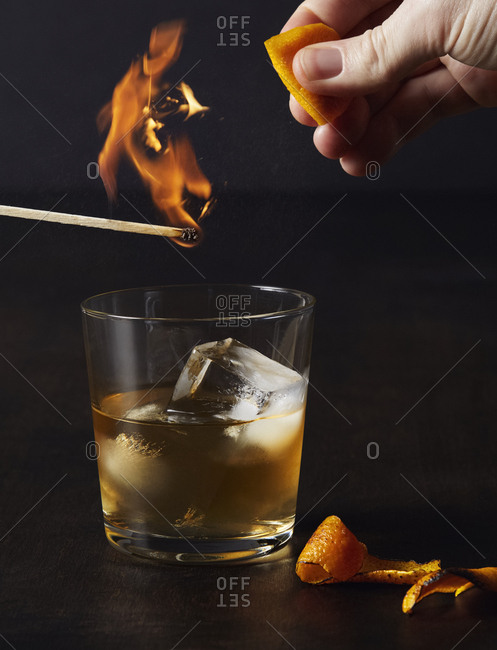 Flaming matchstick with Mezcal old fashioned drink