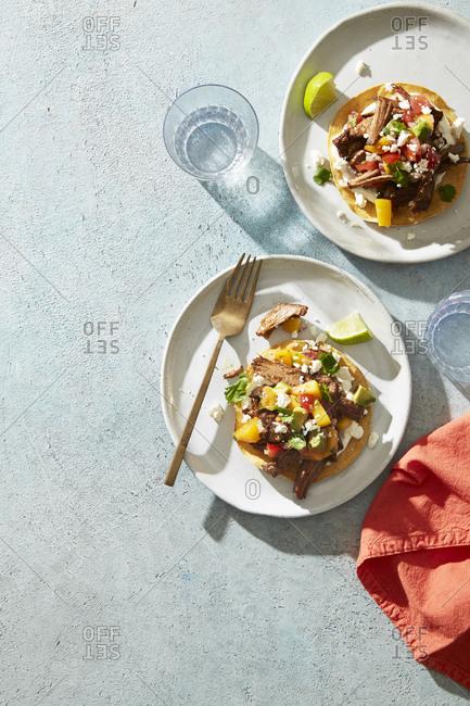 Carnitas tostada served with mango salsa, queso fresco, cilantro, and lime
