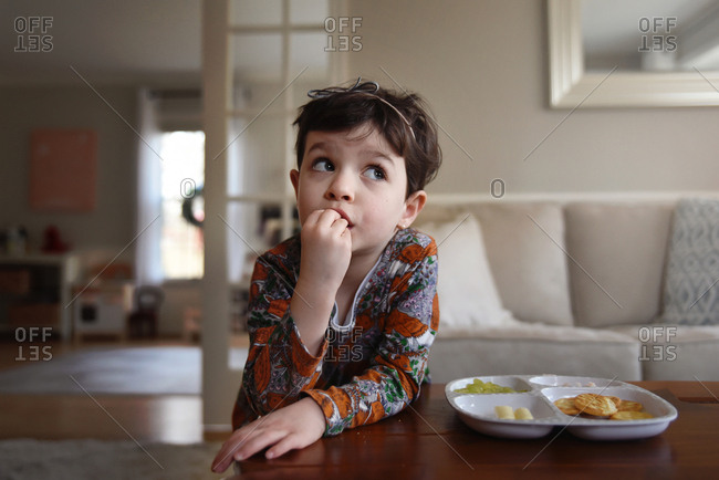 Little girl eats snack in the living room