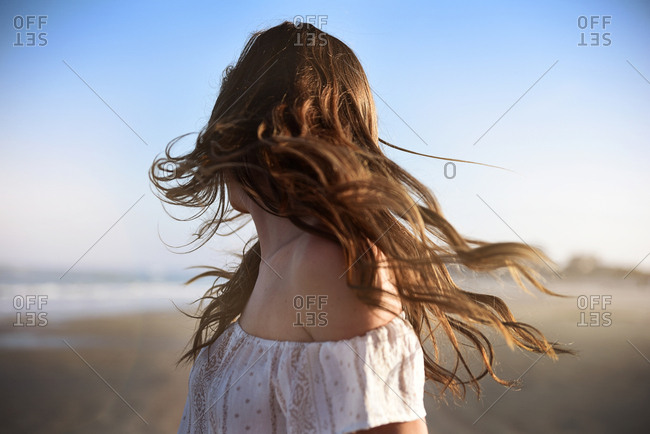A young woman flips her hair on the beach at sunset