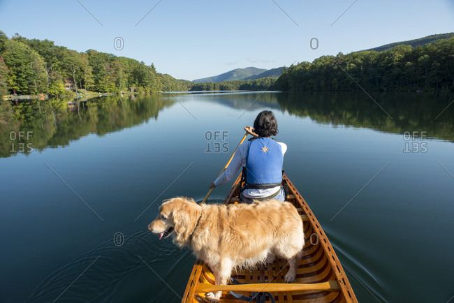 Dog and woman canoeing on scenic Fern Lake