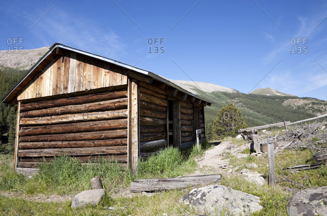 Log cabin in a clearing in mountain landscape