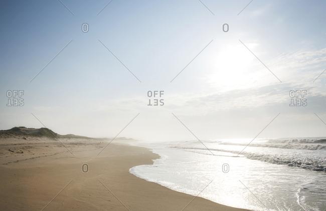 Sea mist hanging over broad empty beach