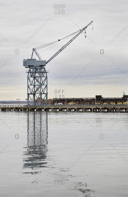 Large gantry crane on pier next to warehouses under renovation