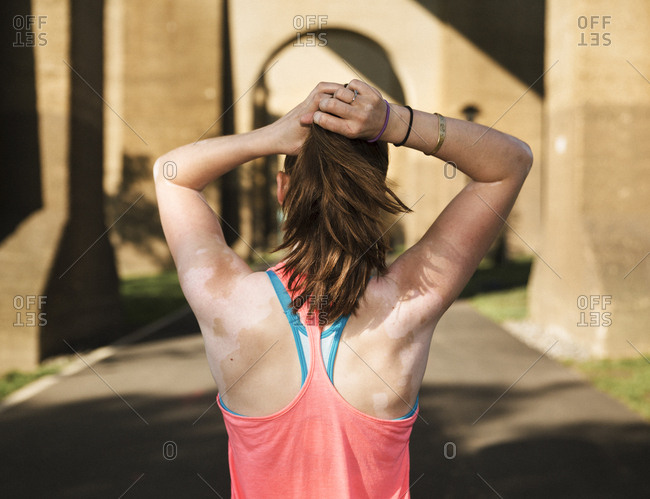 Rearview of young woman in sportswear with sunburned and peeling shoulders tying up hair
