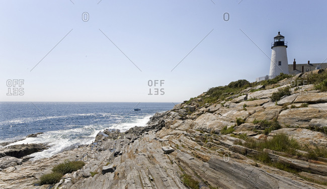 Light house perched on rocky headland keeping watch over the ocean