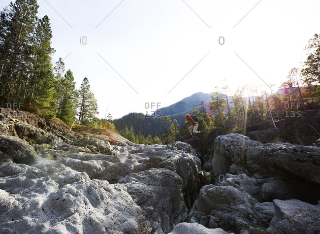 Hiker leaping over narrow rocky gorge on Vancouver Island