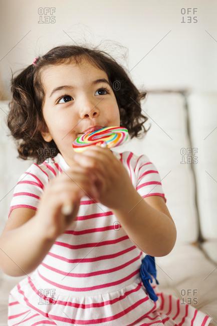 Little girl looking up enjoying her lollipop