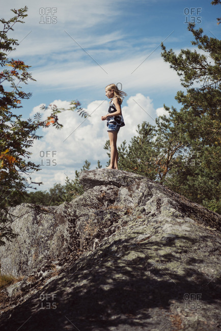 Girl (10-11) standing on top of rock