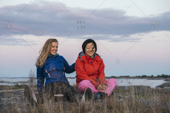 Two women sitting in grass at sunset