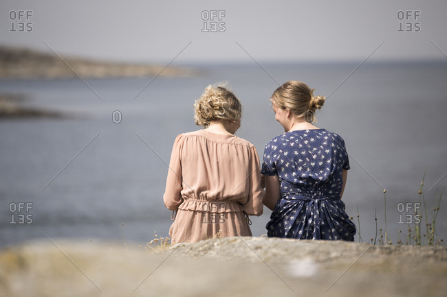 Two young women sitting on cliff and talking