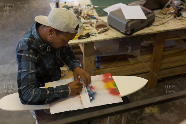 Man making skateboard in workshop
