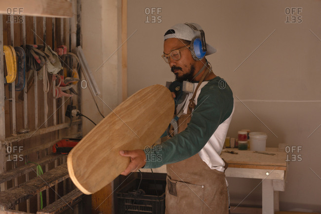 Man examining a skateboard in workshop