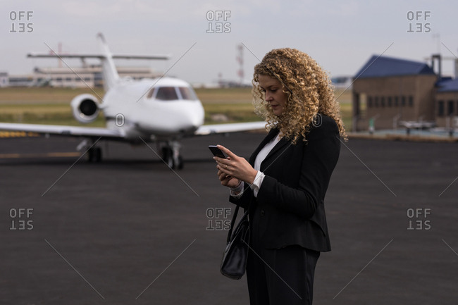 Beautiful businesswoman using mobile phone at terminal
