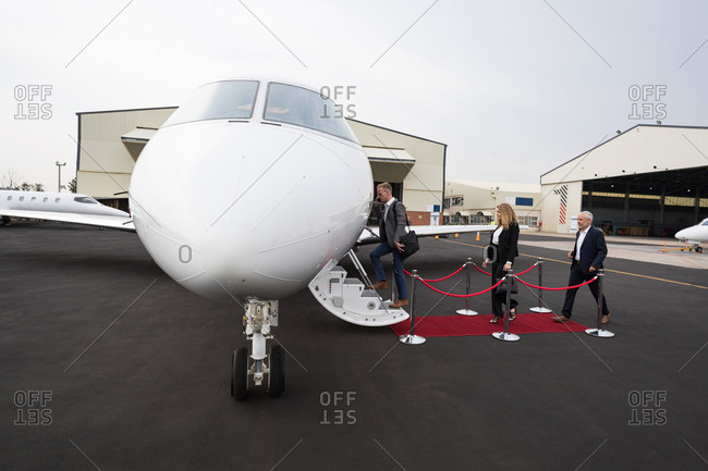 Businesspeople boarding in private jet at terminal