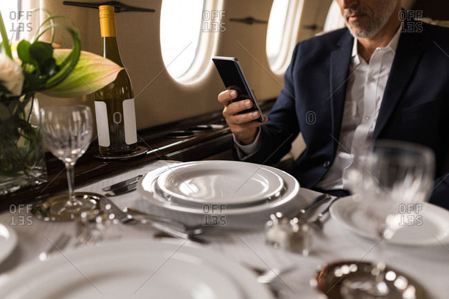 Mid section of businessman using mobile phone in private jet