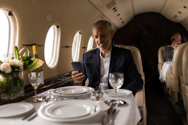 Senior businessman using mobile phone in private jet