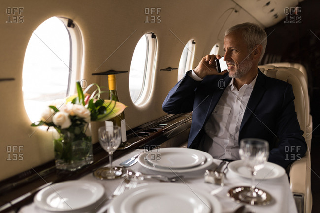 Senior businessman talking on mobile phone in private jet