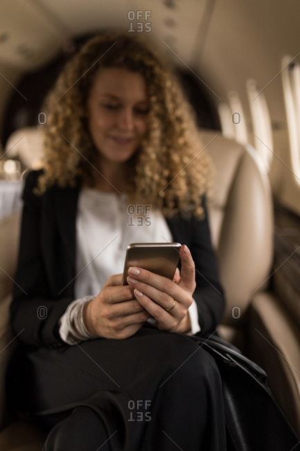 Beautiful businesswoman using mobile phone in private jet