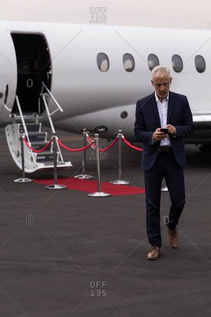 Senior businessman using mobile phone while leaving private jet