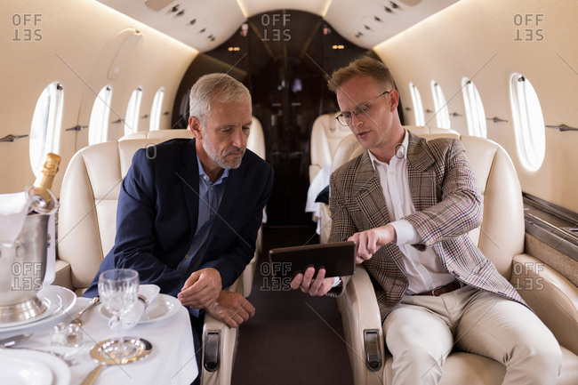 Businesspeople discussing over digital tablet in private jet