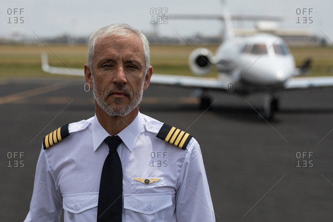 Portrait of senior male pilot standing on a runaway