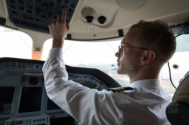 Male pilot pushing button in private cockpit