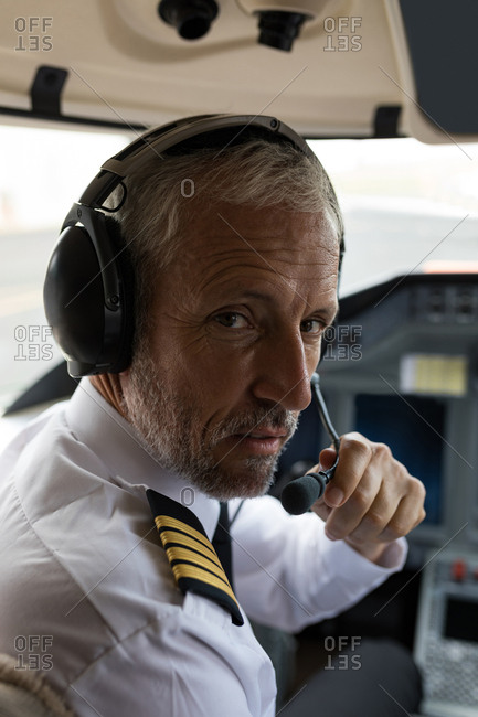 Portrait of male pilot speaking on headset in cockpit