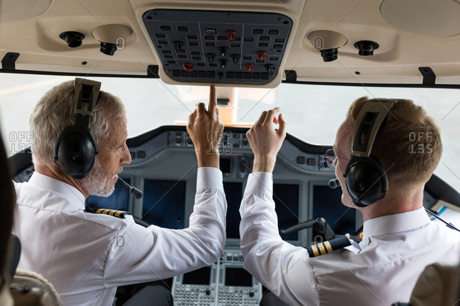 Two male pilots pushing button in private cockpit