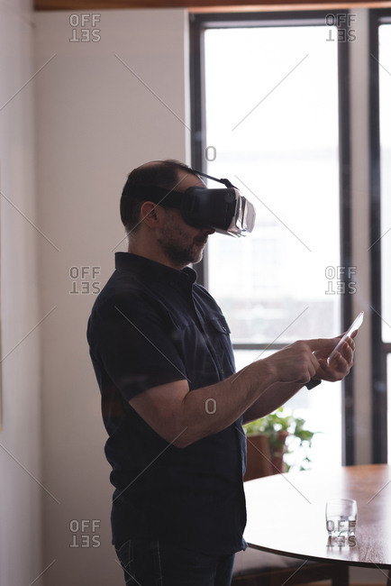 Male executive using virtual reality headset with glass digital tablet in office