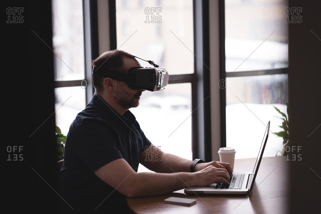 Male executive using virtual reality headset with laptop at desk in office