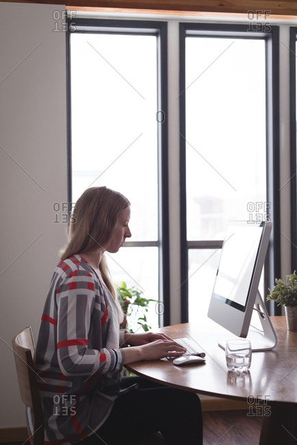 Female executive working on computer at desk in office