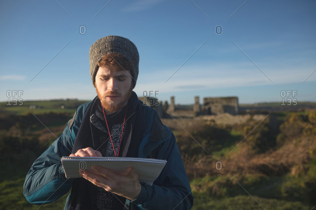 Young male hiker standing with notepad at countryside