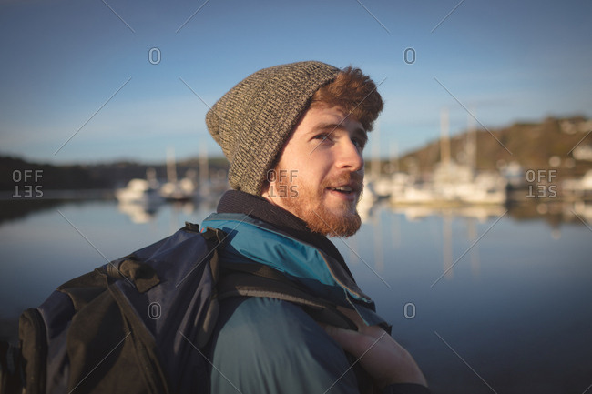 Young male hiker standing with backpack near lake