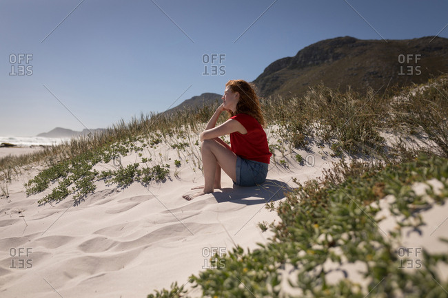Side view of woman sitting on sand at beach on a sunny day