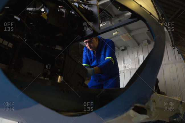 Engineer examining cockpit in aerospace hanger