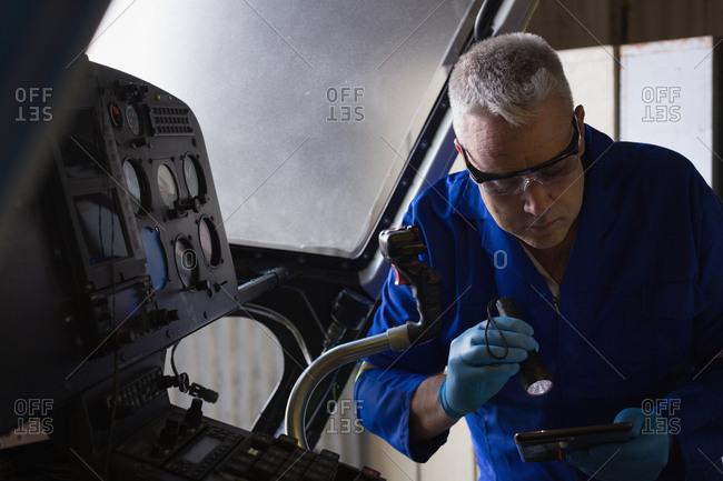 Engineer examining cockpit in aerospace hanger