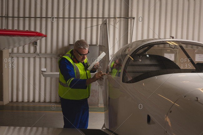 Engineer examining aircraft part in aerospace hangar