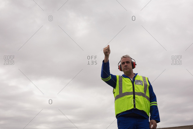 Crew member showing thumbs up in airport