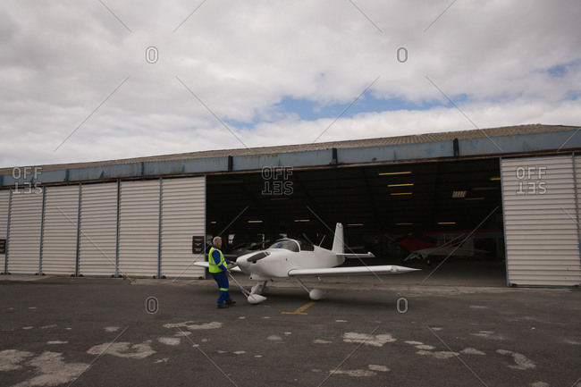 Rear view of crew member taking out aircraft from hangar